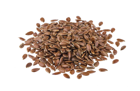 Pile of flax seeds isolated on white background close-up
