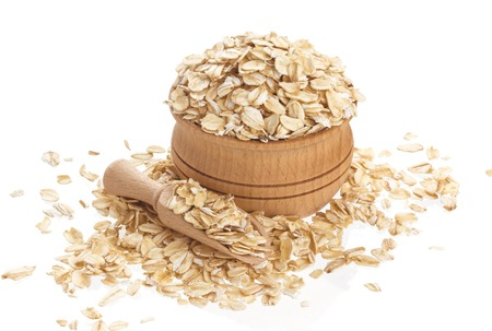 Isolated oatmeal. Oat flakes in wooden bowl on white background Stock Photo