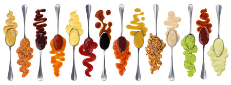 Set of different sauces with spoons isolated on white background Stock Photo