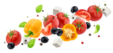 Falling greek salad isolated on white background with clipping path, flying fresh vegetable salad ingredient Imagens