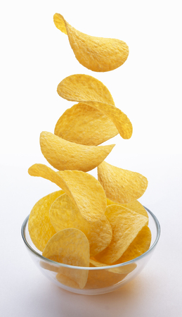 Potato chips falling into glass bowl isolated on white background