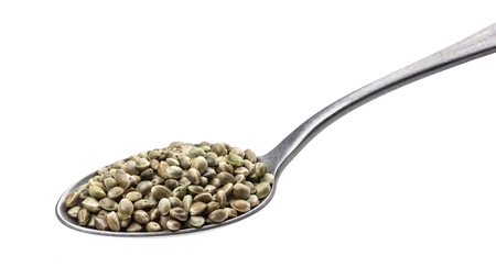 Hemp seeds in spoon isolated on white background, close up, macro