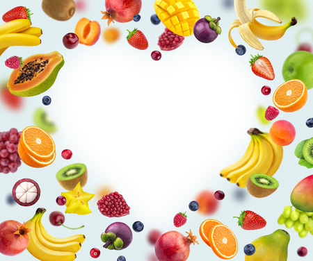 Heart shape frame made of different fruits and berries, isolated on white background Stock Photo