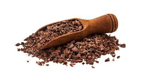 Geriebene Schokolade. Haufen gemahlener Schokolade mit Holzschaufel auf weißem Hintergrund, Nahaufnahme