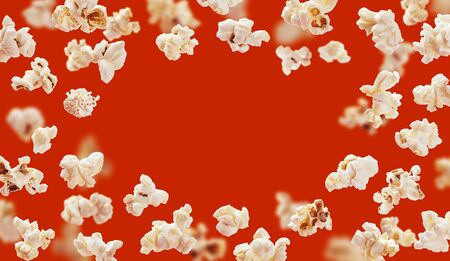 Popcorn frame with space for text, flying popcorn isolated on red background with copy space, movie poster concept 版權商用圖片