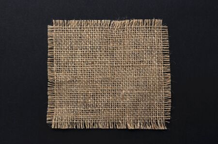 Old burlap fabric napkin closeup. Rough linen jute, sackcloth piece isolated on black background. Hessian texture, sack material, top view