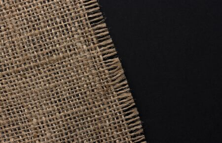 Old burlap fabric napkin on black background, top view