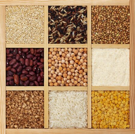 Different types of groats in square wooden box, collection of raw cereals, beans and seeds, top view textures