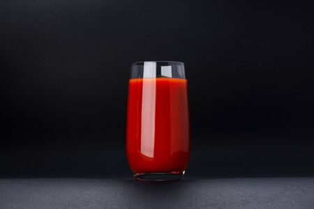 Glass of tomato juice isolated on black background with copy space, bloody Mary cocktail