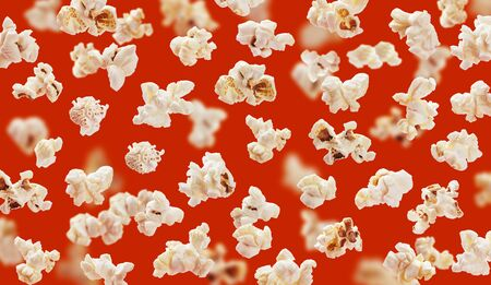 Delicious pop corn grains closeup on red background