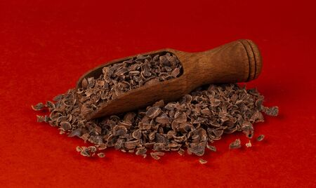 Grated chocolate. Pile of ground chocolate in wooden scoop isolated on red color background with clipping path, closeup 스톡 콘텐츠