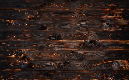 Burnt wooden board, black charcoal wood texture, burned coal barbecue background with copy space, top view Фото со стока