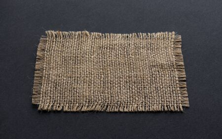 Old burlap fabric napkin closeup. Rough linen jute, sackcloth piece isolated on black background, hessian texture cloth