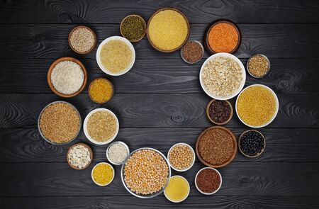 Round frame of cereals, grains, seeds, groats, legumes and beans in bowls, high fiber diet concept, top view of porridge collection on black wooden background with copy space on table, healthy vegetarian food