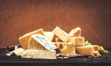 Different types of cheese on black wooden table background. Heap of cheddar, parmesan, emmental, blue cheese. Copy space, photo filtered in vintage style