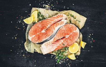 Salmon steaks on black wooden background, red fish, top view, photo filtered in vintage style