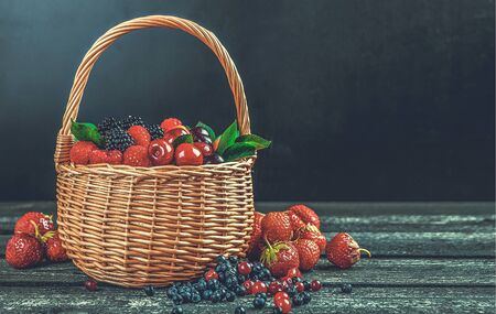 Fresh forest berries in basket on black wooden background with copy space, photo filtered in vintage style