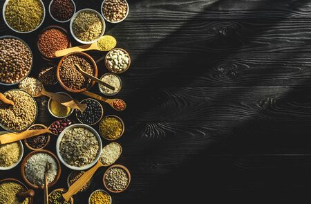 Various cereals, grains, seeds and beans, high fibre diet concept, top view of porridge collection on black wooden background with copy space, healthy vegetarian food, photo filtered in vintage style