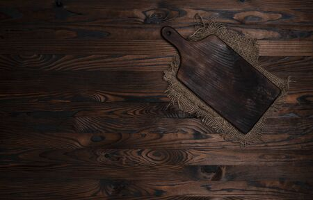 Cutting board with burlap napkin on brown wooden background, top view. Rough linen jute, sackcloth piece on dark wooden table Reklamní fotografie