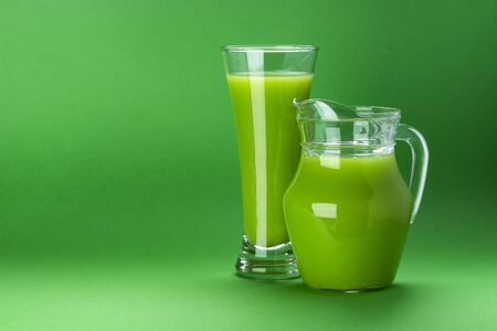 Glass of green juice isolated on color background with copy space for text, fresh apple and celery cocktail, healthy drink concept