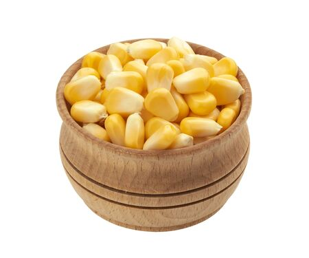 Fresh corn seeds in wooden bowl isolated on white background with clipping path, pile of raw yellow corn grains