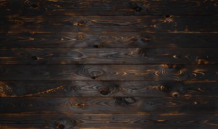 Burnt wooden board texture, black burned background with copy space, top view