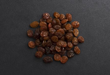 Pile of dried raisins on black background Imagens