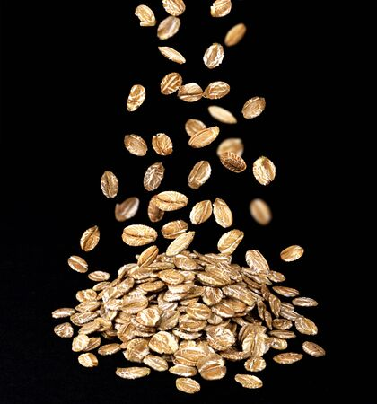 Falling oat flakes isolated on black background, small heap of rye flakes cereal, oatmeal close up