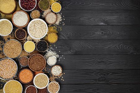 Different cereals, grains, seeds, groats, legumes and beans in bowls, top view of raw porridge collection on black wooden background with copy space Stockfoto