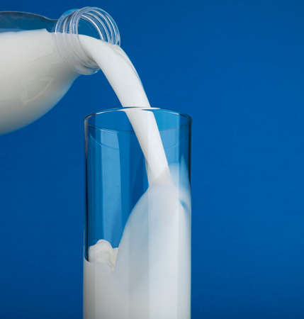 Pouring milk in glass with splash isolated on blue background Foto de archivo