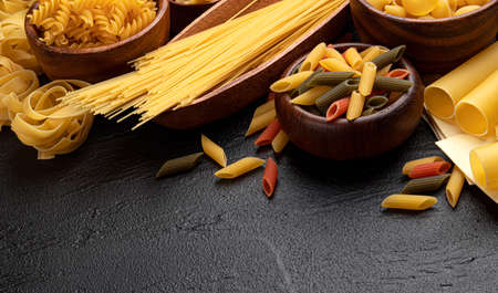 Different pasta types on black background with copy space for text, italian food ingredients concept, top view of dried mixed pasta collection on dark stone table Banque d'images