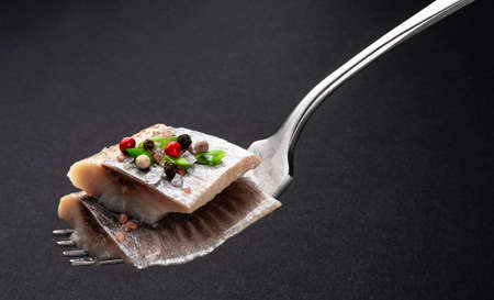 Pieces of salted herring on fork on black background, slices of smoked mackerel fish fillet with salt and spices