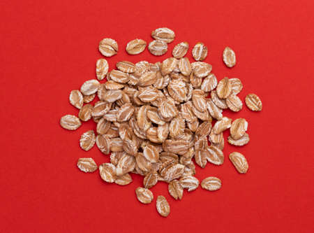 Pile of oat rye flakes on red color background, top view