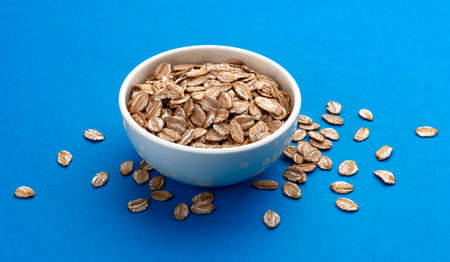 Oat rye flakes in bowl isolated on blue color background with clipping path Stock fotó