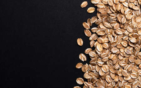 Pile of oat rye flakes on black background, top view with copy space Stock fotó