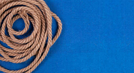 Twisted rope on blue canvas background, top view with copy space