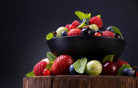 Mix of wild berries on black background 免版税图像