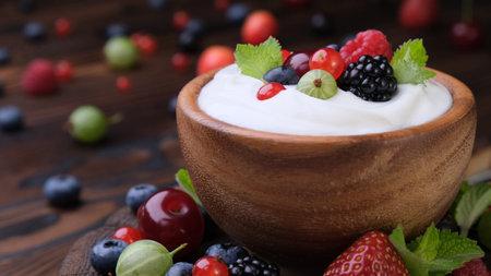 Bowl of yogurt with wild berries on dark wooden background