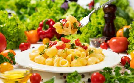 Plate of italian pasta, pipe rigate on fork with tomatoes and basil