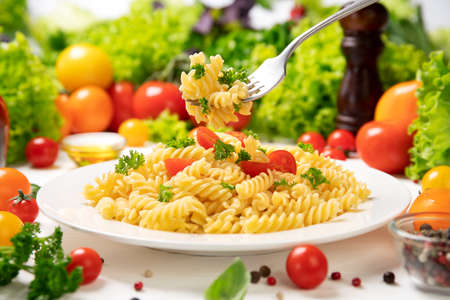 Plate of cooked italian fusilli pasta with tomatoes and basil leaves Stok Fotoğraf
