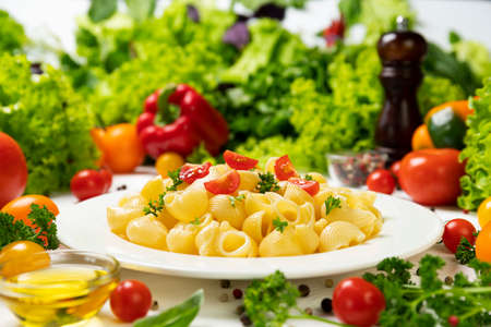 Italian pipe rigate pasta with tomatoes and basil leaves Stok Fotoğraf