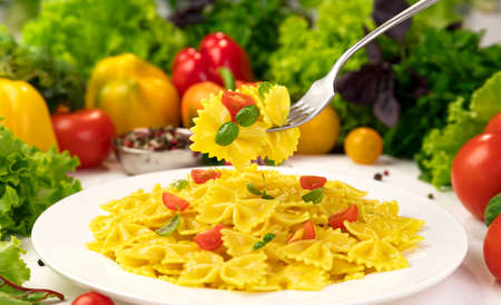 Plate of italian pasta, farfalle on fork with tomatoes and basil Stok Fotoğraf