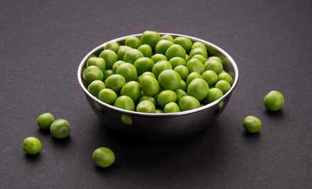 Bowl of fresh green peas on black background