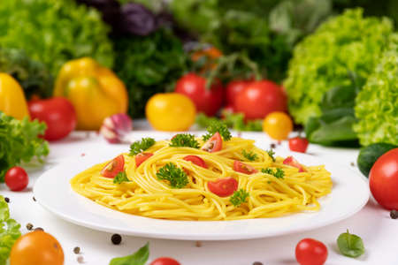 Plate of italian pasta, spaghetti with tomatoes and basil leaves