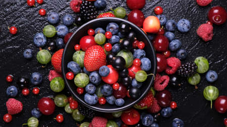 Collection of wild berries on black background, top view
