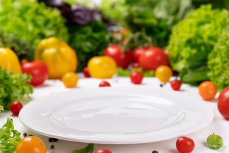Fresh organic vegetable ingredients for cooking around empty white plate Stok Fotoğraf