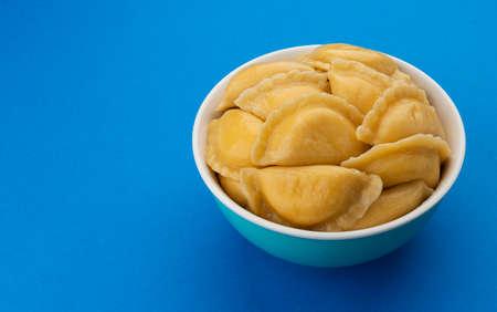 Filled dumplings, russian vareniki, pelmeni on blue background