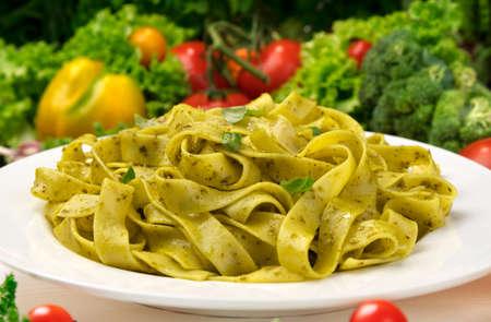 Cooked italian fettuccine pasta with pesto sauce