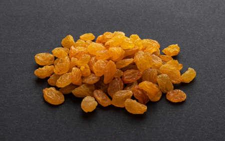 Golden raisins on black background Фото со стока