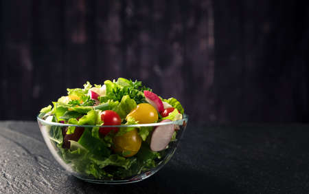 Vegetable salad on black background with copy space 免版税图像